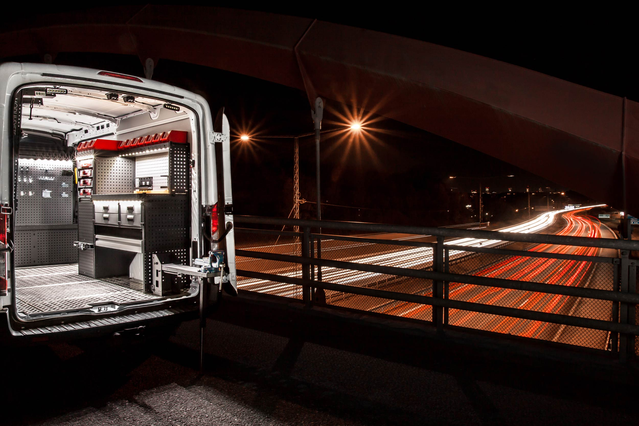 Electrician's van fitted out with modul-system van racking on the job at night
