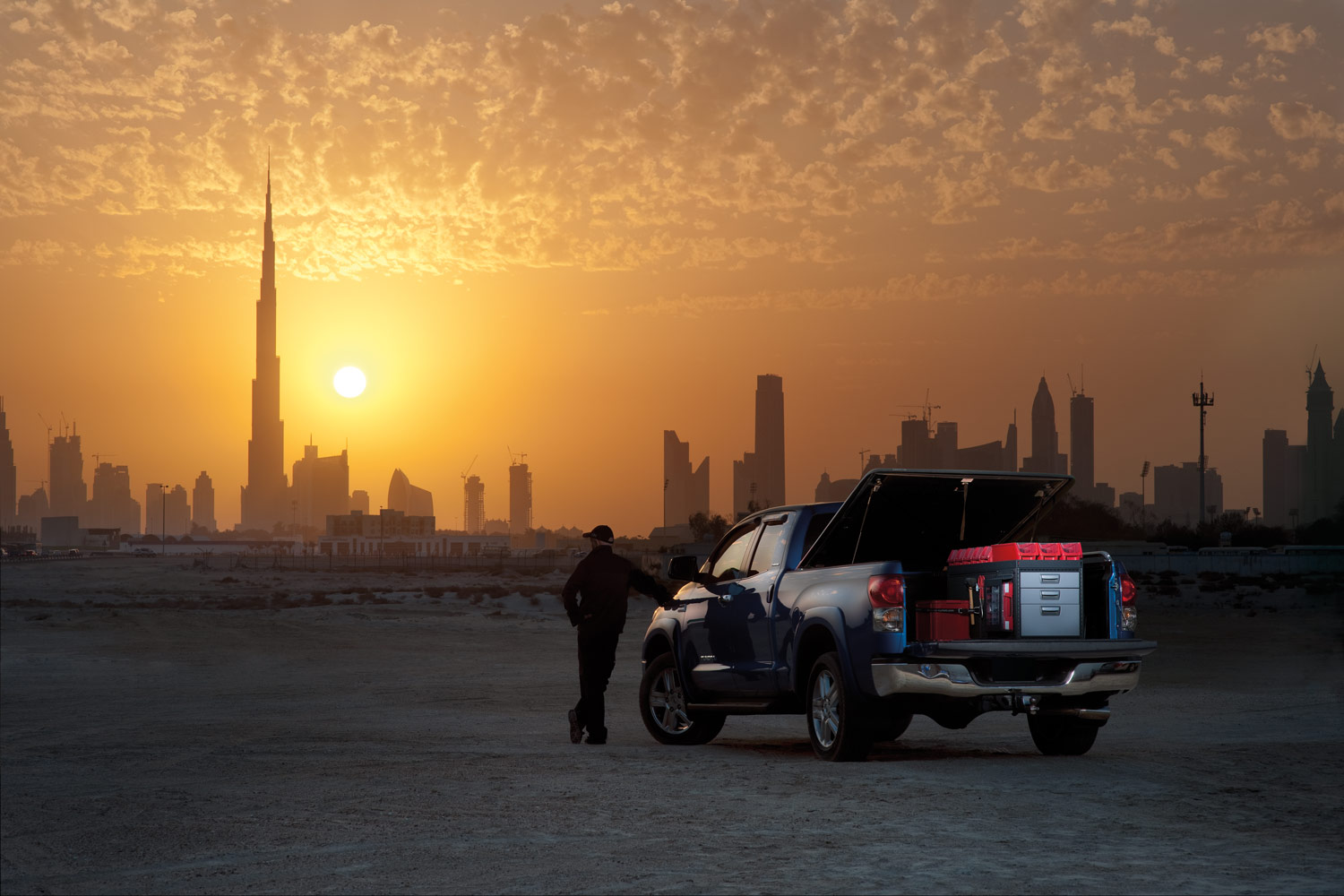 Worker's blue pickup truck with modul-system racking in a desert facing a sunset
